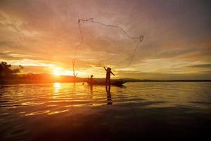 Silhouette Fisherman Fishing by using Net photo