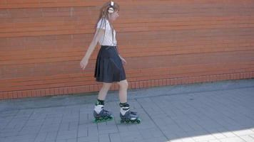 Young woman with headphones rollerblading on the streets video