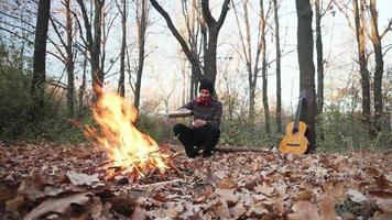 Young male traveler in the autumn forest play on guitar alone video