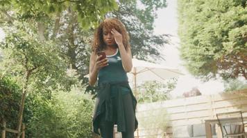 Woman wearing sportswear standing in garden watches smartphone video