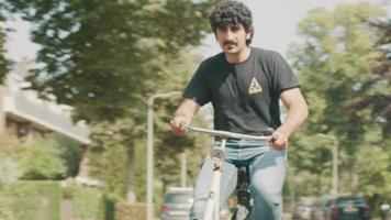 Hombre en bicicleta en el suburbio dando la vuelta a la esquina video