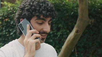 homme debout dans le jardin parlant sur smartphone video