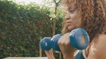 Woman standing in garden lifting dumbbells video