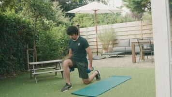 Man in garden holding dumbbells kneeling with one leg forward video
