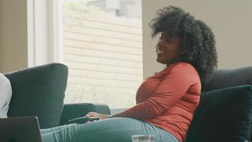 kvinna som sitter på soffan med fjärrkontrollen och skrattar video