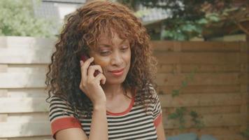 Femme debout dans le jardin parlant vivement sur smartphone video