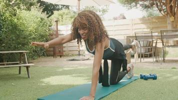 Woman in garden doing yoga postures on mat video