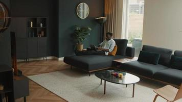Man sitting on couch with laptop scrolling and talking video