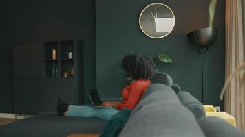 Woman on sofa typing on laptop video