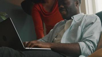 Man sitting with laptop and woman stands next to him video