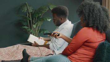 man läser bok och kvinna som använder fjärrkontroll sitter i vardagsrummet video