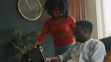 kvinna som stryker katt som står bredvid mannen som sitter i soffan med bärbar dator video