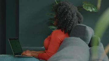 Woman sitting on sofa typing on laptop and laughs video