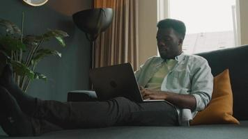 Man sitting on couch with laptop having video call