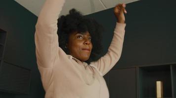 vrouw met koptelefoon en smartphone danst in woonkamer video
