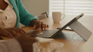 kvinna med bärbar dator hjälper mannen att skriva i anteckningsboken vid bordet video