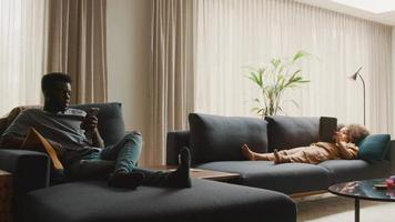man sitter på dagbädd och tittar på smartphone och flicka som ligger på soffan video