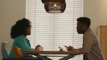 kvinna och man sitter vid bordet och pratar video