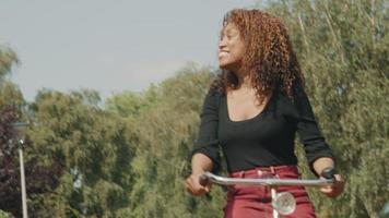 Mujer en bicicleta en el suburbio saludando y llamando video