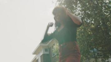 vrouw met koptelefoon lacht en danst op straat video