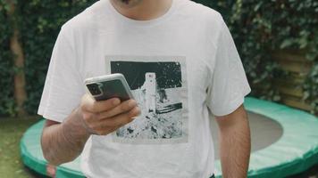 man die in de tuin staat te typen op een smartphone die in de lens kijkt video