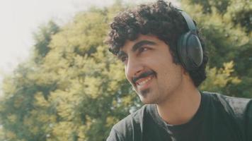 Hombre con auriculares sentado en el jardín con la cabeza móvil y sonriendo video