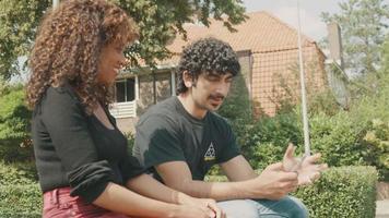 El hombre sostiene el teléfono inteligente y habla de ello con la mujer en el patio delantero. video