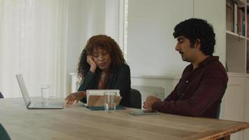 vrouw praat en man luistert zittend aan tafel met laptop en notebook video
