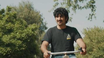 hombre en bicicleta en el suburbio saludando video