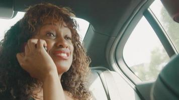 Woman sitting in back of car talking on smartphone video