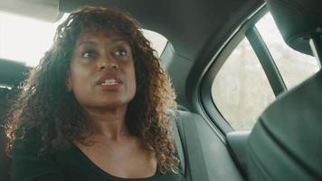 Woman sitting in back of car talking video