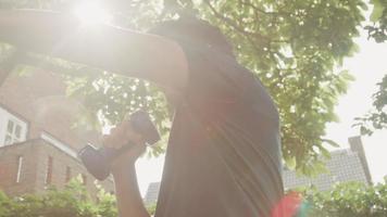 Hombre de pie en el jardín haciendo movimientos de boxeo con mancuernas video