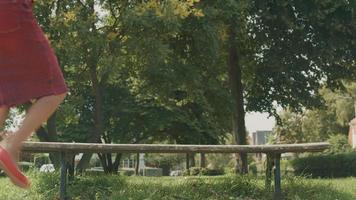 vrouw met koptelefoon gaat zitten op houten bankje bewegend op muziek video