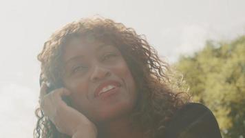 vrouw met koptelefoon zit in de tuin enthousiast te bewegen video