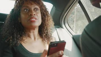Woman sitting in back of car talks and looks at smartphone video
