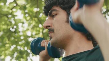 Man standing in garden lifting dumbbells video