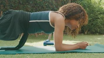 Woman doing planking exercise on grass video