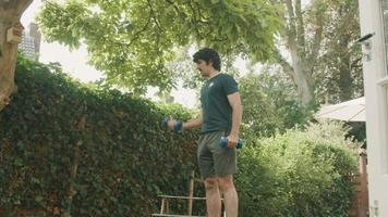 Hombre de pie en el jardín levantando pesas video