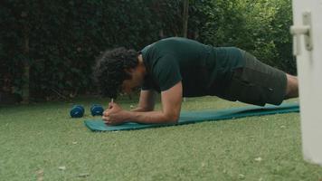 El hombre en el jardín termina el ejercicio de entarimado se levanta y guarda la alfombra video