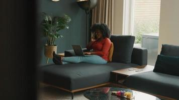 Woman sitting on couch with laptop talking on smartphone video
