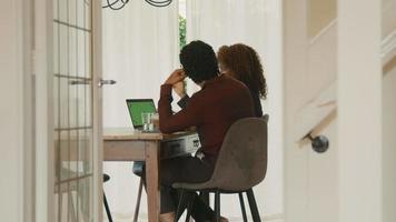vrouw en man praten aan tafel met een groen scherm laptop video