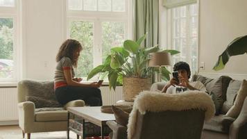 kvinna och man pratar i vardagsrummet som håller smartphones i händerna video