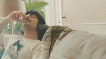 un homme avec un casque assis sur un canapé bouge la tête au rythme en profitant de la musique video
