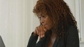 mulher sentada à mesa digitando no laptop video