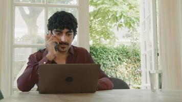 Man sitting at table with laptop talking on smartphone video