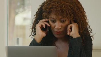 femme assise à table avec un ordinateur portable parlant sur smartphone video