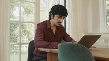 Hombre sentado a la mesa escribiendo en la computadora portátil y viendo el teléfono inteligente video