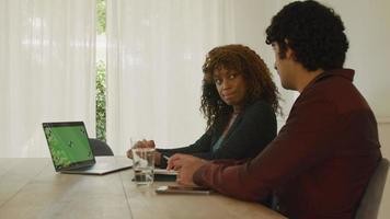 vrouw en man in gesprek aan tafel met groen scherm op laptop video