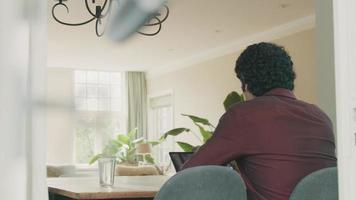 homem sentado à mesa com videochamada no laptop video