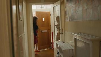 La mujer abre la puerta que entra al pasillo, deja las llaves y camina hacia las escaleras. video